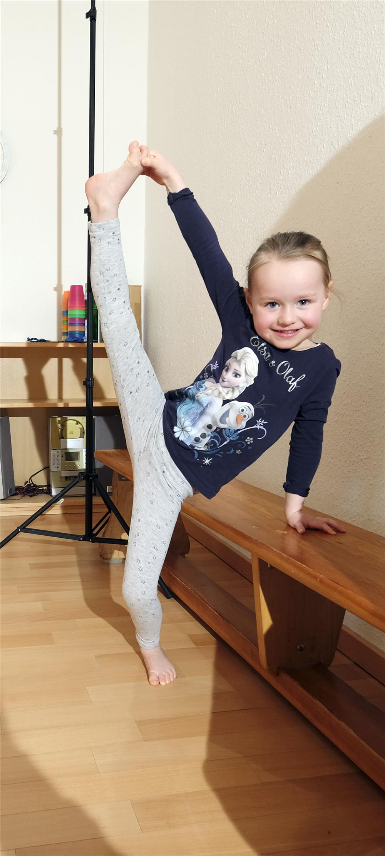 Ein Kleines Mädchen Hebt Ihr Bein Zum Spagat über Den Kopf / D. Wäsche